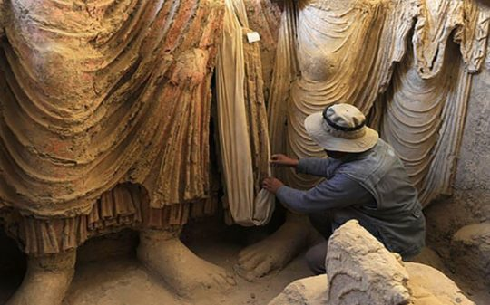 statues examined by archaeologist