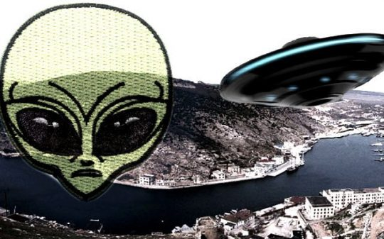 black ufo flying over city