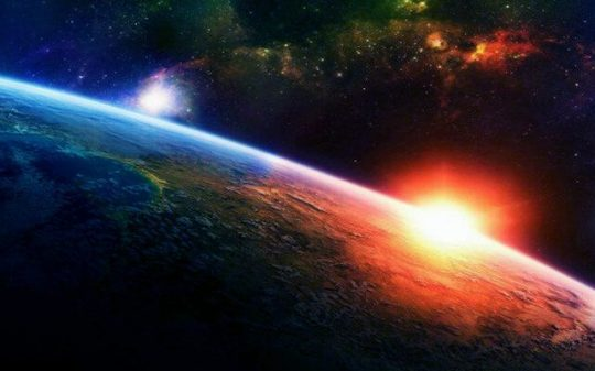rising sun over planet in space